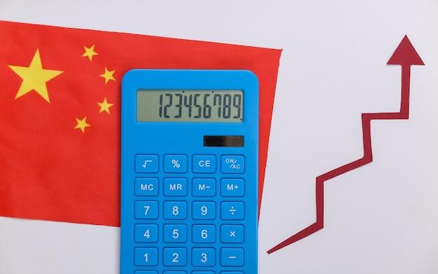 赤い成長矢印と電卓が付いた中国の旗。上向き矢印グラフ。経済成長