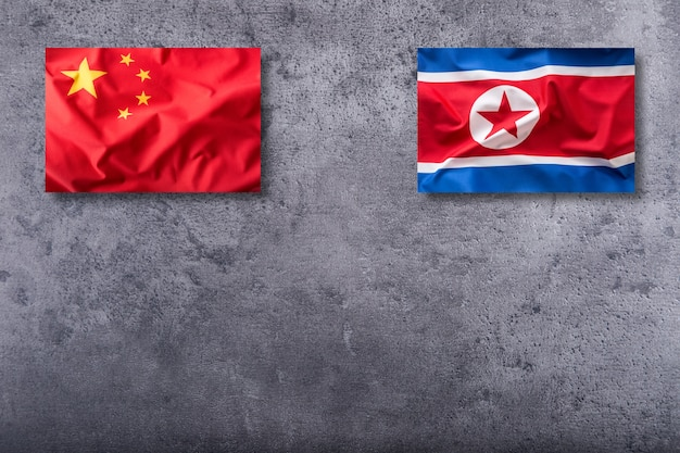 China and north korea flag on concrete background.