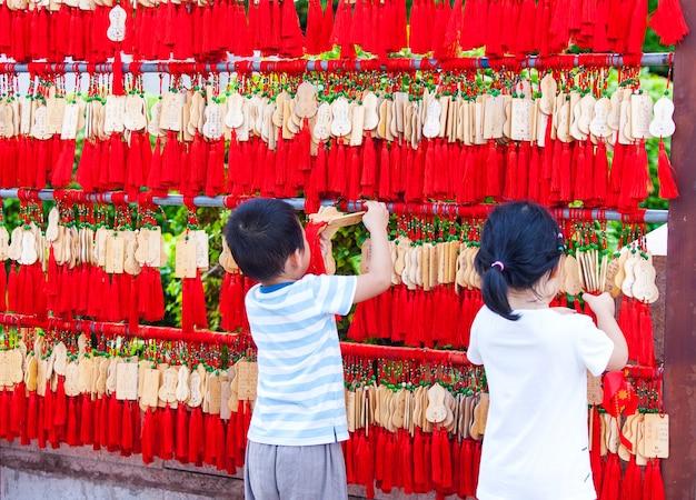 중국, 싼야 - 2017년 11월 15일: 중국 어린이들이 불교 사원에서 ema를 교수형에 처합니다.