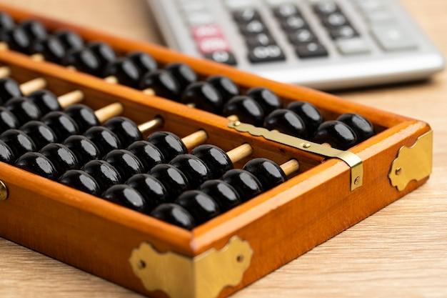 茶色の木のテーブルの正面図とコピースペースに計算機と中国のそろばんヴィンテージ
