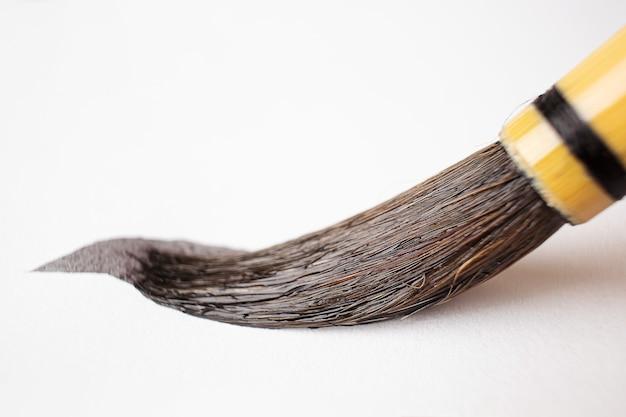 흰 종이에 중국 아트 브러쉬 잉크입니다. 그림 그리기, 교육 도구의 개념. 매크로 사진.