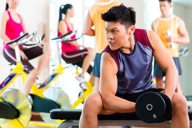 Китайско-азиатская группа мужчин и женщин, занимающихся спортивными упражнениями или тренировками в фитнес-зале со штангой и гантелями для большей мощности