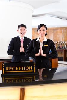 高級ホテルのフロントデスクにある中国のアジアのレセプションチームが、典型的なジェスチャー、優れたサービスとおもてなしのサインでゲストをお迎えします