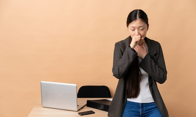 Chinese business woman in her workplace coughing a lot