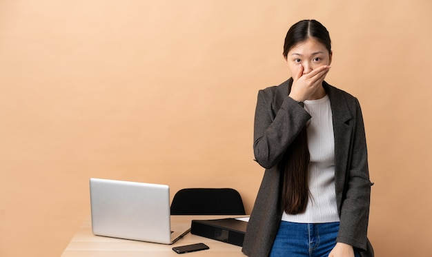 Chinese business woman in her workplace covering mouth with hand