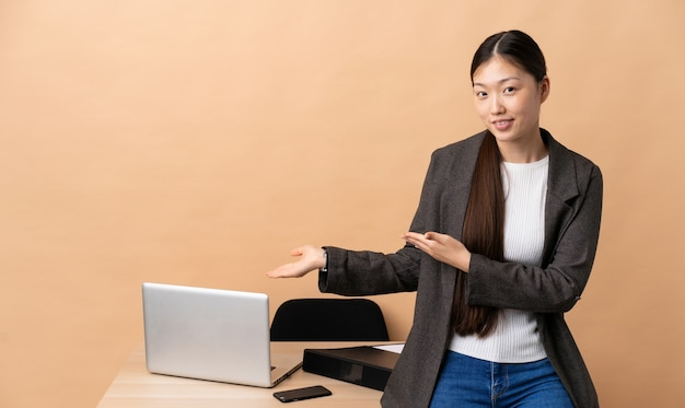 Chinese business woman in her workplace extending hands to the side for inviting to come