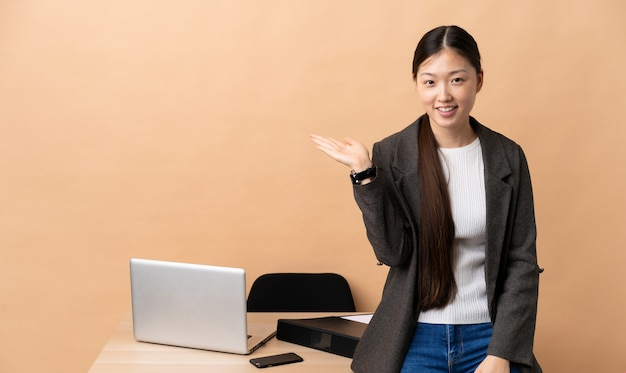 Chinese business woman in her workplace holding copyspace imaginary on the palm to insert an ad