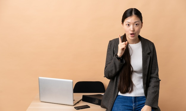 Chinese business woman in her workplace intending to realizes the solution while lifting a finger up