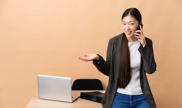 Chinese business woman in her workplace keeping a conversation with the mobile phone with someone