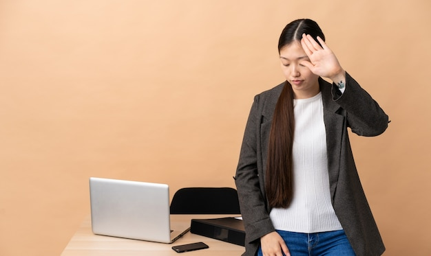 Chinese business woman in her workplace making stop gesture and disappointed