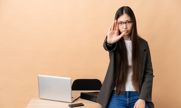 Chinese business woman in her workplace making stop gesture