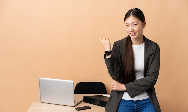 Chinese business woman in her workplace pointing finger to the side