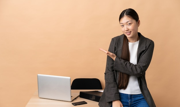 Chinese business woman in her workplace presenting an idea while looking smiling towards