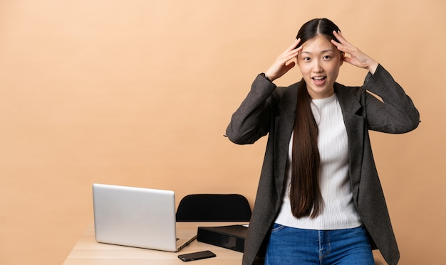 Chinese business woman in her workplace with surprise expression