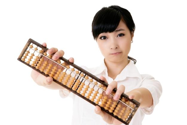 白い背景に伝統的なそろばんを保持している中国のビジネス女性。 Premium写真