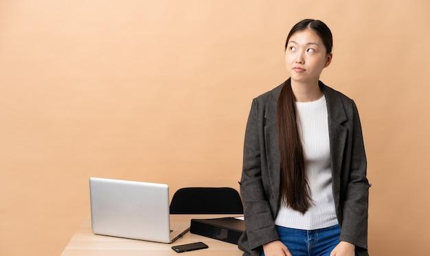 Китайская деловая женщина на своем рабочем месте и глядя вверх
