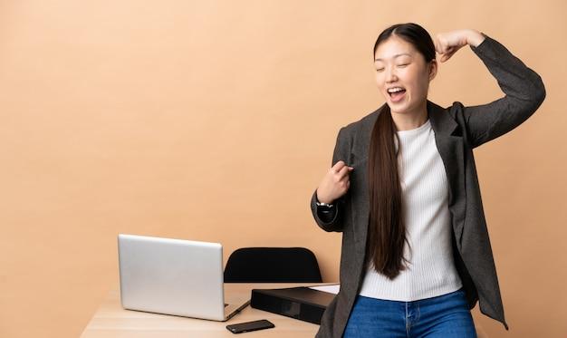 Китайская деловая женщина на своем рабочем месте, празднует победу
