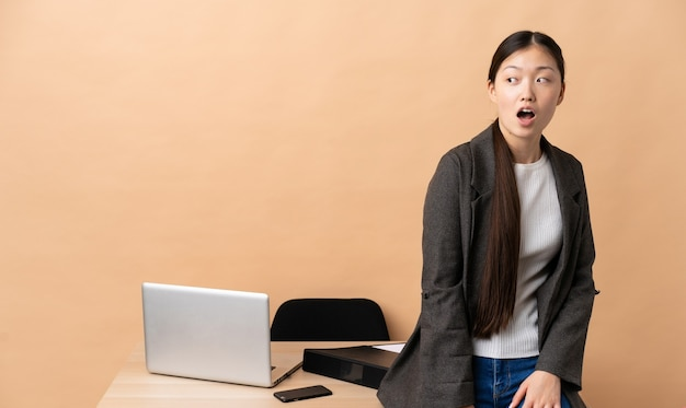 Китайская деловая женщина на своем рабочем месте делает неожиданный жест, глядя в сторону