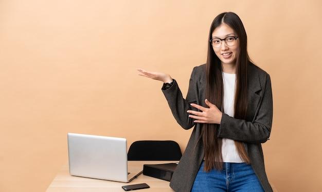 그녀의 직장에서 중국 비즈니스 여성이 와서 초대하기 위해 손을 옆으로 확장