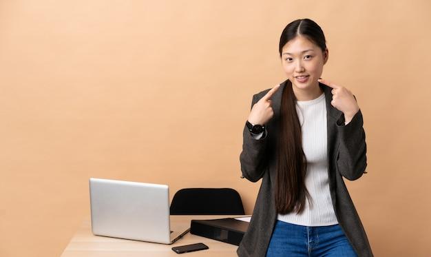 Китайская деловая женщина на ее рабочем месте, давая пальцы вверх жест