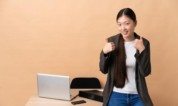 제스처를 엄지 손가락을주는 그녀의 직장에서 중국 비즈니스 우먼