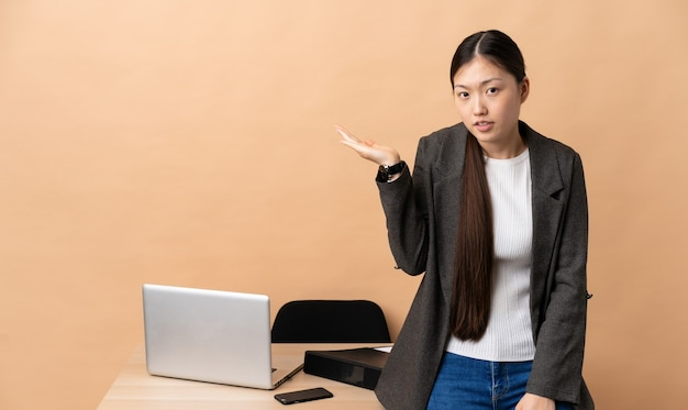 彼女の職場で疑問を持っている中国のビジネスウーマン