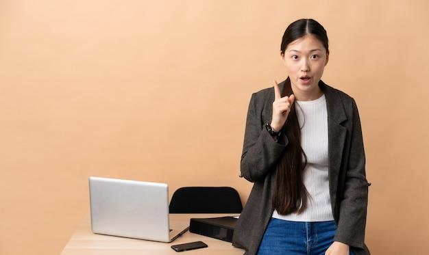그녀의 직장에서 중국 비즈니스 여성은 손가락을 들어 올리면서 솔루션을 실현하려고