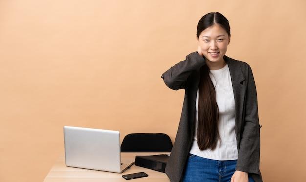 Китайская деловая женщина на своем рабочем месте смеется