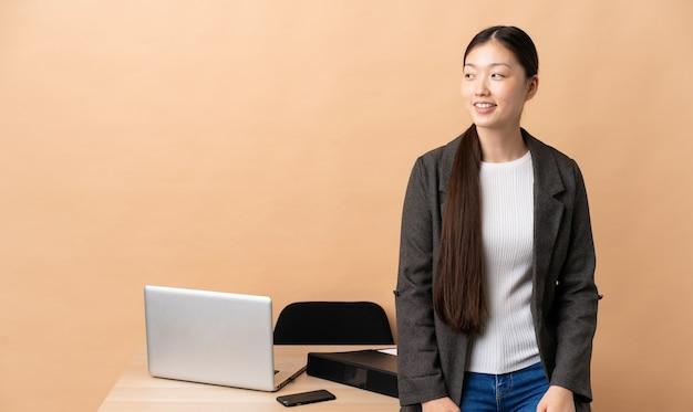 Китайская деловая женщина на своем рабочем месте смотрит сторону