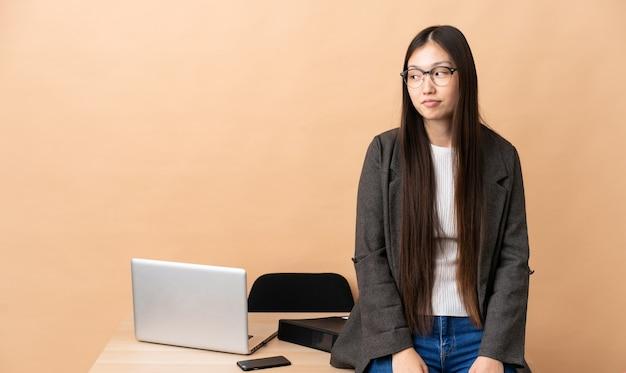그녀의 직장에서 중국 비즈니스 우먼 측면을 찾고 의심 제스처를 만드는