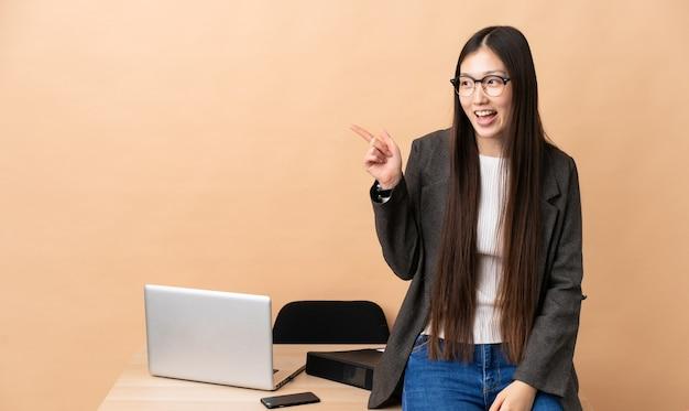Китайская деловая женщина на своем рабочем месте, указывая пальцем