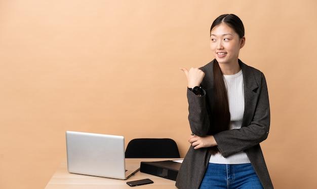 제품을 제시하기 위해 측면을 가리키는 그녀의 직장에서 중국 비즈니스 우먼