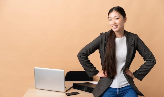 그녀의 직장에서 중국 비즈니스 여자 엉덩이에 팔을 포즈와 미소