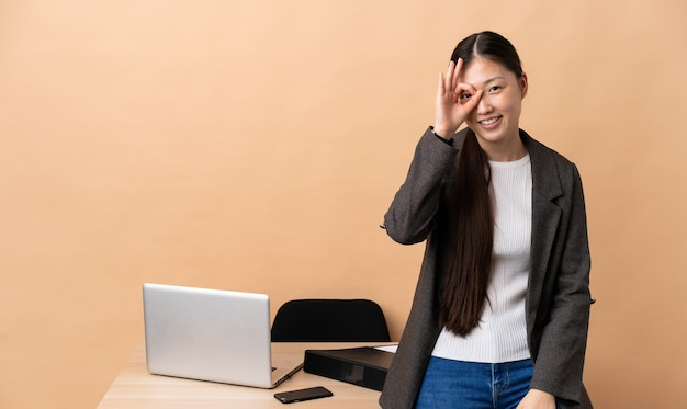 Китайская деловая женщина на своем рабочем месте, показывая пальцами знак ок