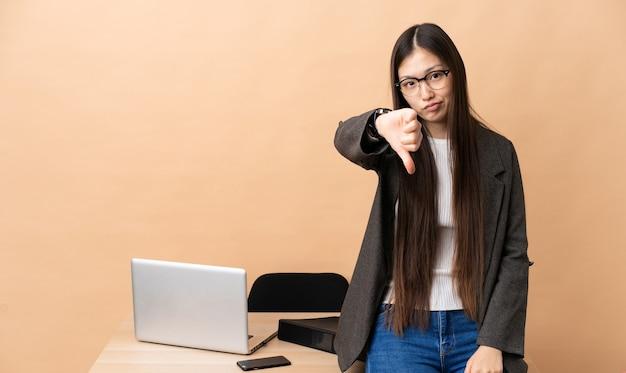 Китайская деловая женщина на своем рабочем месте показывает палец вниз с негативным выражением лица