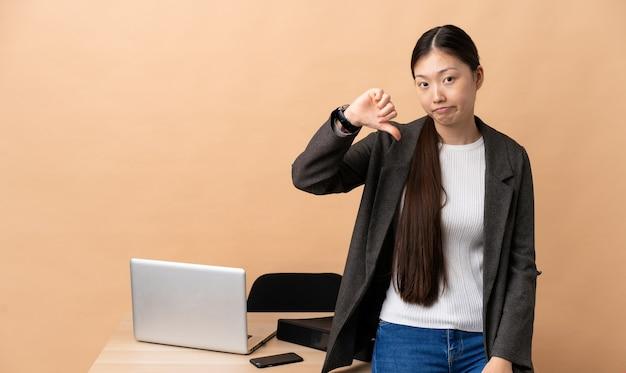 부정적인 표정으로 아래로 엄지 손가락을 보여주는 그녀의 직장에서 중국 비즈니스 우먼