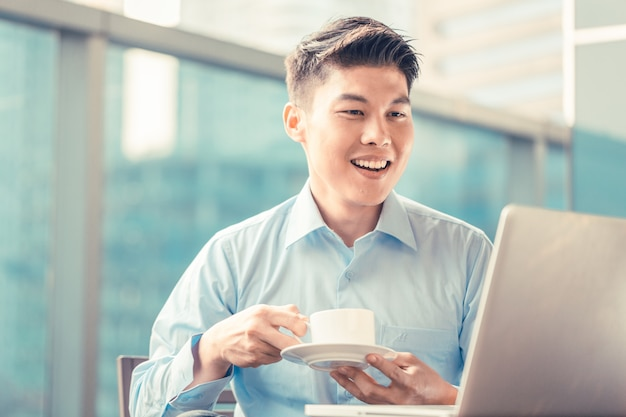 Chinese businessman having coffee at his laptop sitting in front
