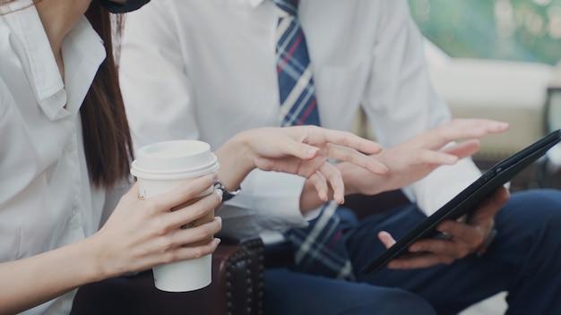 座って若い日本のビジネスマンと話す中国の実業家は、会議で一緒にフェイスマスクのアドバイスを着用します