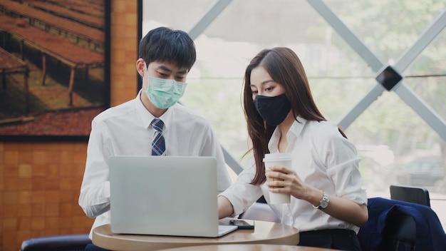 座って若い男と話す中国の実業家は、会議で一緒にフェイスマスクのアドバイスを着用します