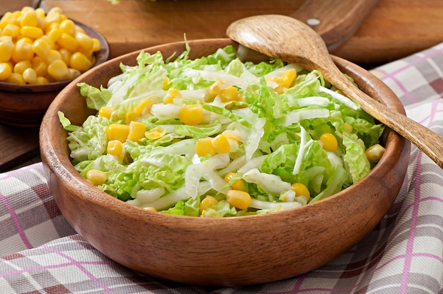 Chinese cabbage salad with sweet corn in a wooden bowl