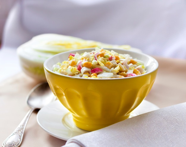 Chinese cabbage, sweet corn and surimi salad in a yellow bowl