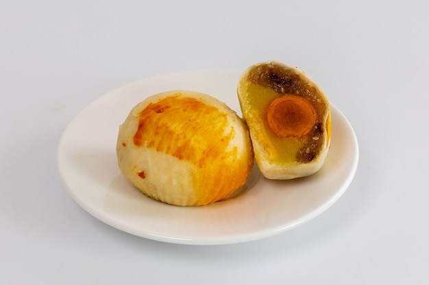 Chinese cake or moon cake filled with mashed mung bean and salted egg yolk on white background