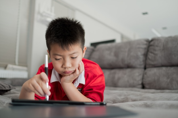 中国の子供中毒電話、スマートフォンをしているアジアの少年、子供が電話を使う、スマートフォンを見ている