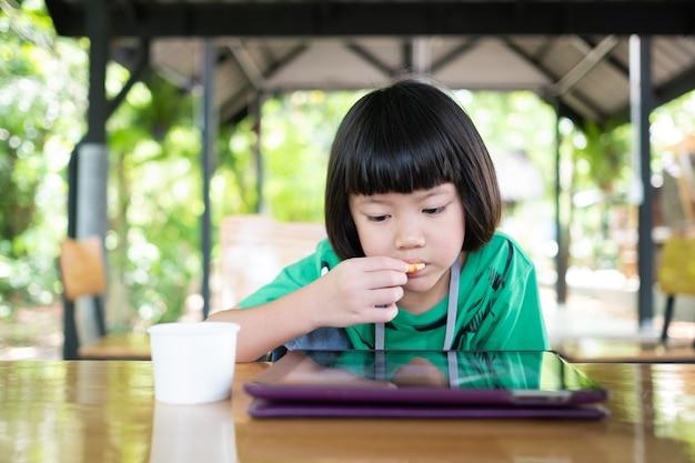 Китайский ребенок пристрастился к телефону, азиатская девушка играет в смартфон, ребенок смотрит мультфильм