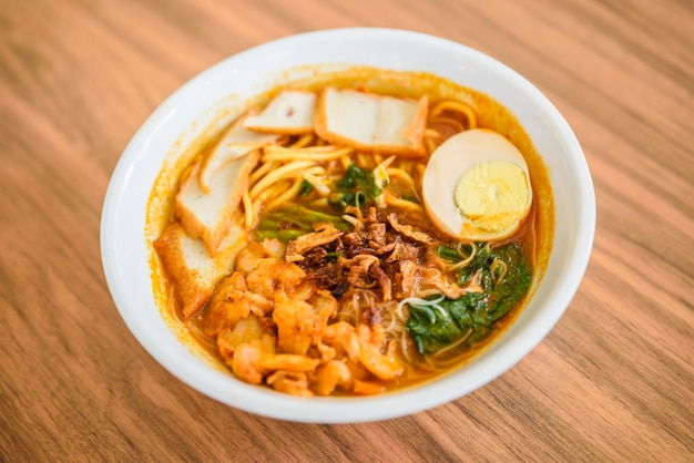Chinese chopsticks eating noodle, a famous malaysia prawn noodle cerry soup.
