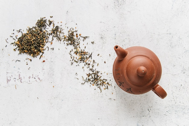 Chinese clay teapot with herbs on white concrete backdrop