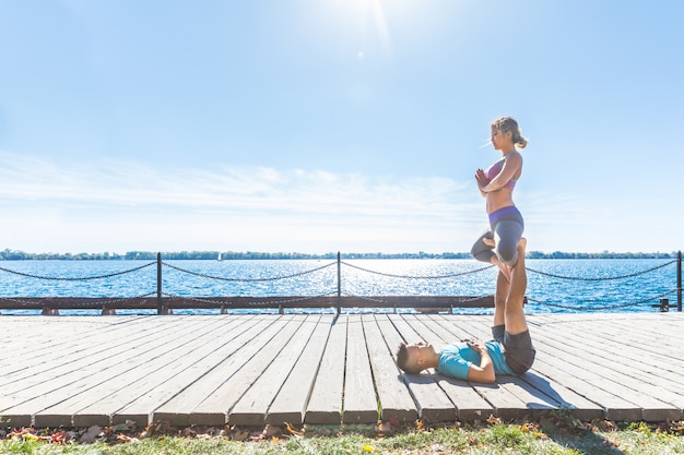 Chinese couple practicing acrobatic yoga at park in toronto
