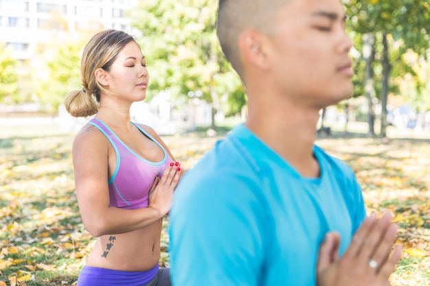 Chinese couple practicing yoga at park in toronto