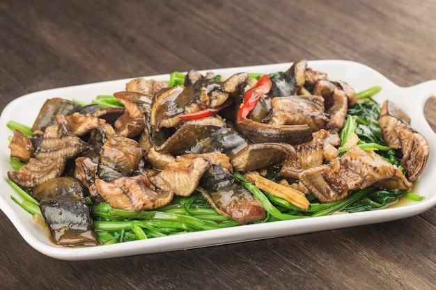 Китайская кухня: жареный угорь с тарелкой капусты