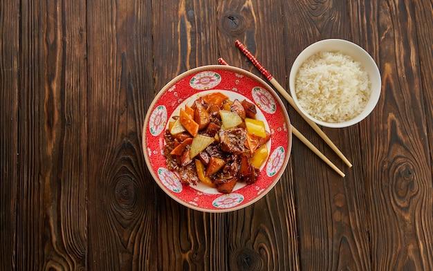 中華料理、ピーマン、タマネギ、パイナップルを添えた甘酸っぱい揚げ豚肉のチャンクを箸で伝統的な皿に、古い木製のテーブルに白いボウルにご飯を入れて